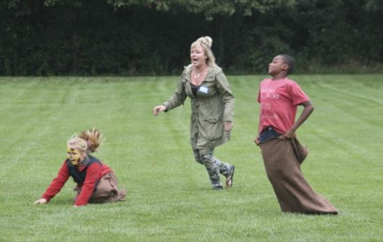 2 young girls in a potato sack race with an adult running with them.