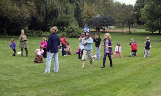 A group of kids and supervisors in the park playing games