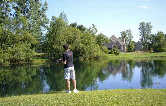 Man gazing on the pond with trees in the background